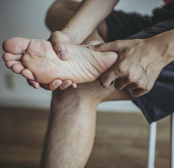 Man sitting in chair rubbing foot due to peripheral neuropathy in Los Angeles, CA