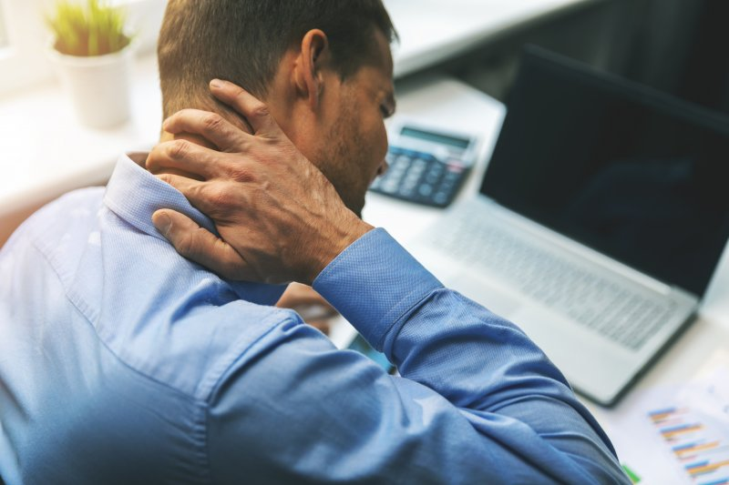 Man at desk rubbing his neck in pain