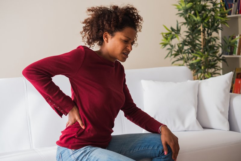 Woman on couch with her back pain